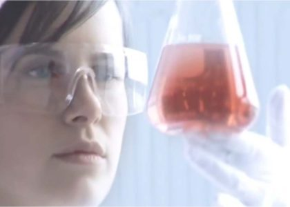 This is a photograph of a young woman examining a beaker full of red liquid.