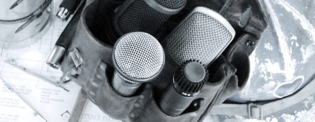 Photograph of microphones in a leather tool pouch with a hardhat.