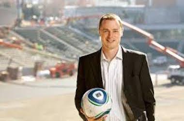 Merritt Paulson holds soccer ball in stadium under construction